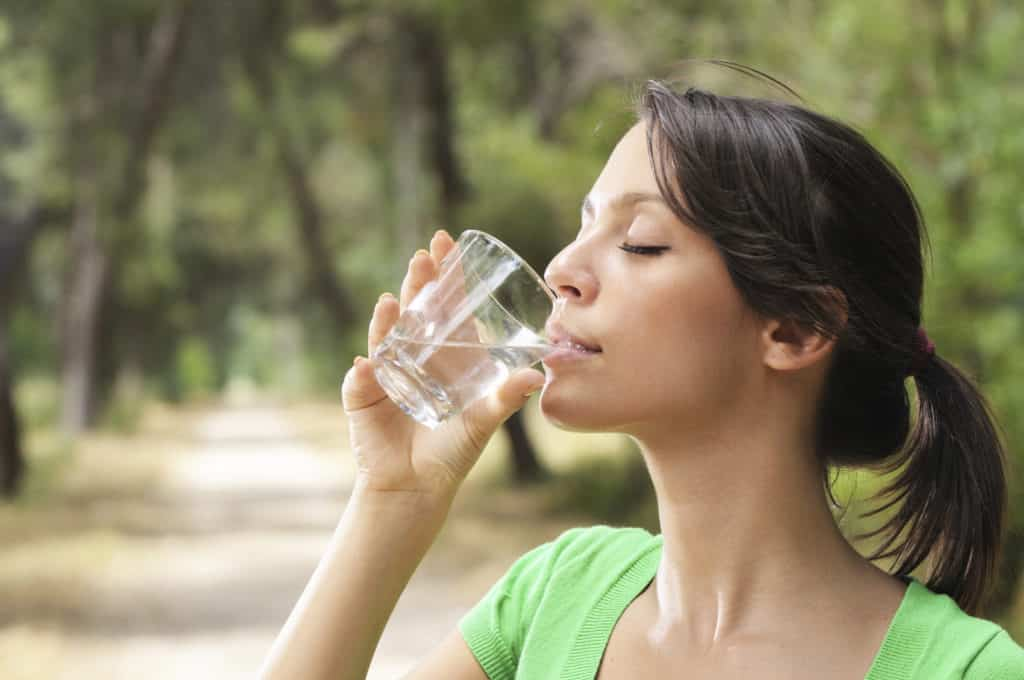 young woman drinking with waterglass
